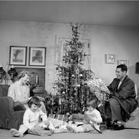 Family with two children (4-6) opening gifts by Christmas tree
